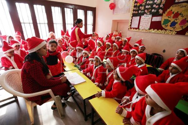 children dressed in santa claus costumes sit in their class as part of christmas celebrations in