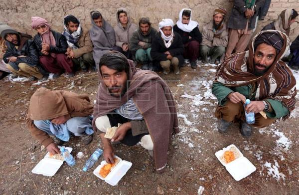 (FILE) Afghan people affected by floods have a meal, near their temporary shelter in Guzara district of Herat province, Afghanistan, 19 February 2017. EPA/JALIL REZAYEE