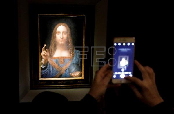 "People take pictures of the painting ""Salvator Mundi"" believed to be by Leonardo da Vinci (circa 1500) during a public preview before an auctioning of the painting at Christie's auction house in New York, New York, USA, Nov. 15, 2017. EPA-EFE FILE/JUSTIN LANE"
