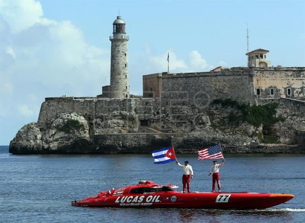 epa06148739 Nigel Hook (R) and Jay Johnson (L), drivers of the speedboat Lucas Oil SilverHook, wave the flags of Cuba (L) and the United States (R) upon their arrival in Havana Harbor, Cuba, after making the journey from Key West, Florida, to Havana in a record time of one hour and 18 minutes on 17 August 017. EPA/Alejandro Ernesto
