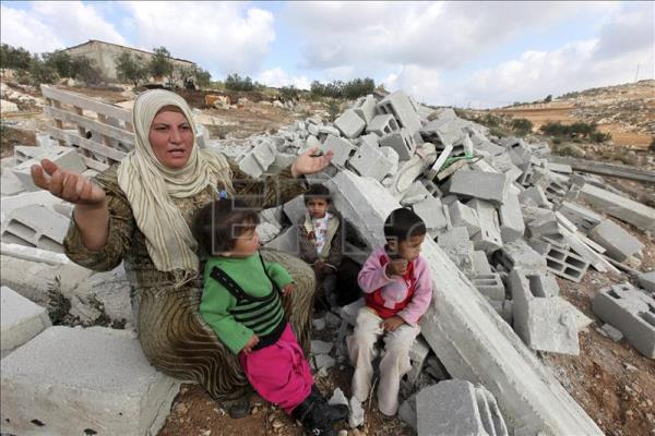 A Palestinian woman next to her children, sitting on the rubble of his house after being demolished, in the village of Yata, near Hebron, West Bank. EFE / File