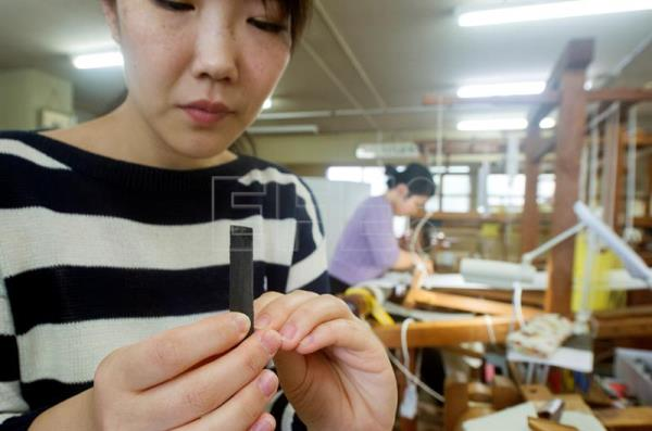 Master nail weaver, Kyoko Kikuchi, uses a file to serrate edges in her finger nails so they can be used to weave tapestry to make traditional kimonos, at the Ishikawa Tsuzure Weaving company in Kyoto, Japan, Apr. 16, 2018.  EPA-EFE/EVERETT KENNEDY BROWN ATTENTION: For the full PHOTO ESSAY text please see Advisory Notice epa06769956