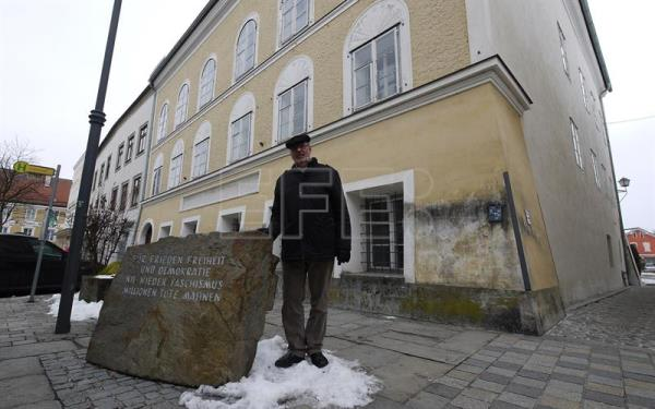 A file picture dated Feb. 5, 2015 shows Florian Kotanko from the Society for Contemporary History stands alongside a plaque in front of the house where Adolf Hitler was born in Braunau am Inn, Austria. EPA/MATTHIAS ROEDER