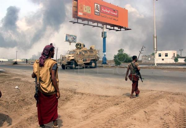 Yemeni government forces patrol as smoke billows from an alleged Houthi position during battles between Yemeni government forces and Houthi rebels in the port city of Hodeidah, Yemen, Sept. 12, 2018. EPA-EFE/NAJEEB ALMAHBOOBI