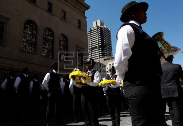 Members of the honor guard carry wreaths during a memorial and wreath laying ceremony for three fire fighters who died fighting a fire in the building above the memorial, in Johannesburg, South Africa, 12 September 2018. EPA/KIM LUDBROOK