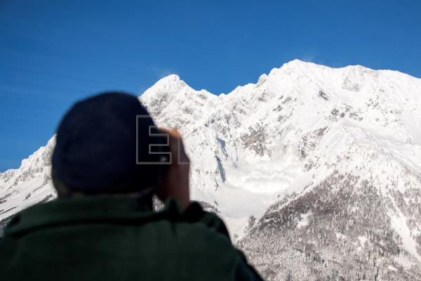 A man watches with his binoculars as an artificially-induced avalanche tumbles towards the valley after explosive material was detonated by the Austrian armed forces at Mount Grimming near Bleiberg, Austria, Jan. 16, 2019. EPA-EFE/CHRISTIAN BRUNA
