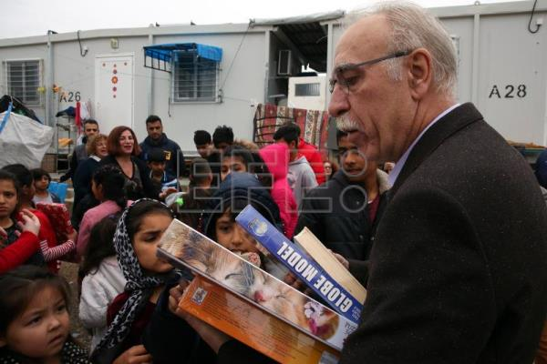 Greek minister delivers presents to migrant children in Athens refugee camp