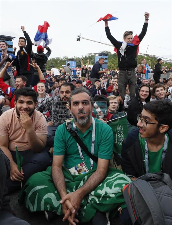 Soccer fans celebrate around dejected fans of Saudi Arabia (C) in the FIFA Fan Fest area in Moscow, Russia, 14 June 2018, after Russia scored a goal in the opening match of the FIFA World Cup 2018 between Russia and Saudia Arabia. EFE