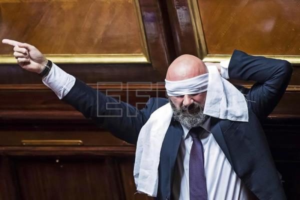 Stefano Lucidi from the anti-establishment 5-Star Movement (M5S) puts a blindfold on during the first of five confidence votes in the Senate on a bill for a new election law, in Rome, Italy, Oct. 25, 2017. EPA-EFE FILE/ANGELO CARCONI