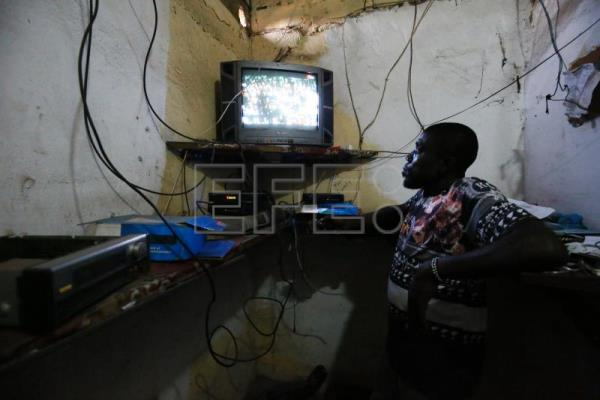 A staff member monitors watches a television during an English Premiere Leaque match inside the control room of the Lagoon Football Cinema at the Newkru Town slum community in Monrovia, Liberia, Feb. 22, 2018. EPA-EFE/AHMED JALLANZO