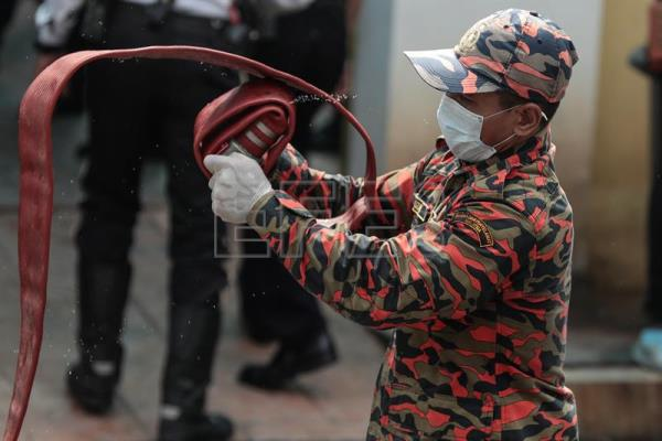 A Fire and Rescue Department officer rolls a fire hose after a fire broke out at a religious school in Jalan Datuk Keramat, Kuala Lumpur, Malaysia, Sept. 14, 2017. EPA-EFE/FAZRY ISMAIL