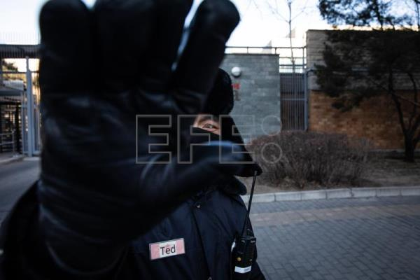 A Chinese security official gestures to stop a photographer from taking photos in front of the Canadian embassy in Beijing, China, Jan. 15, 2019. EPA-EFE FILE/ROMAN PILIPEY