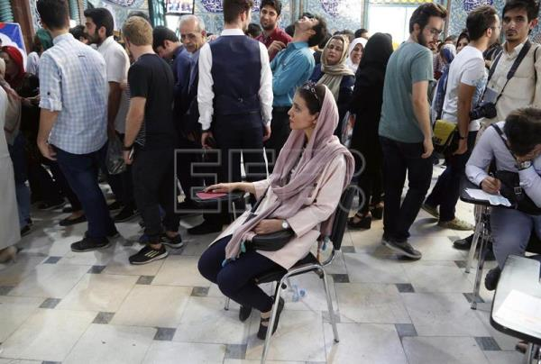 Iranians wait in a line to cast their ballots in the Iranian presidential elections at a polling station in Tehran, Iran, May 19, 2017. EPA/ABEDIN TAHERKENAREH