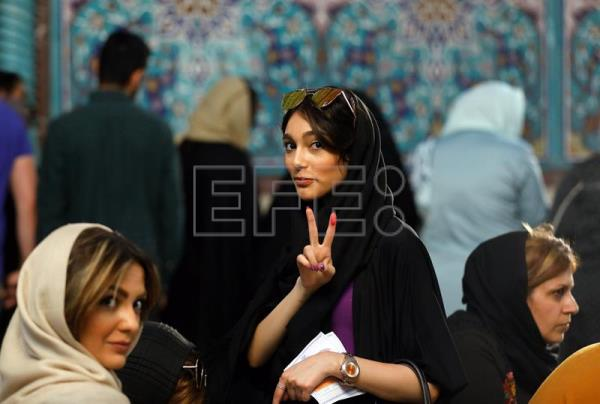 An Iranian woman flashes the victory sign as she waits with others to cast her ballot in the Iranian presidential elections at a polling station in Tehran, Iran, May 19, 2017. EPA/ABEDIN TAHERKENAREH