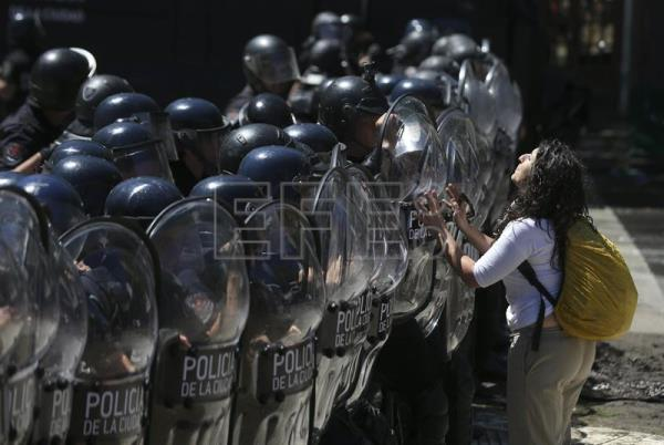 A woman shouts slogans in front of members the Argentinean Federal Police, in Buenos Aires, Argentina, Dec. 18, 2017. EPA-EFE/David Fernandez