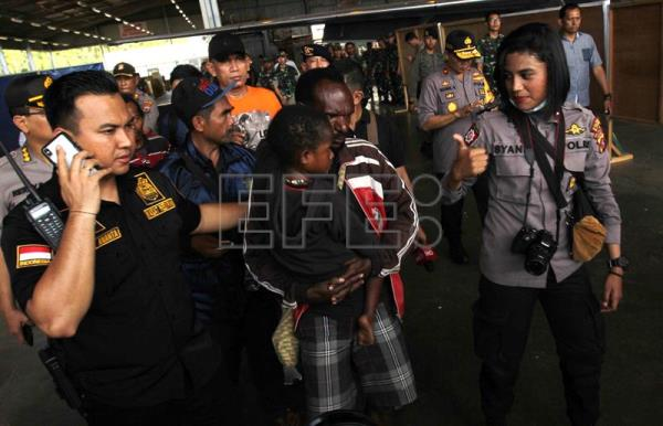 Indonesian police officers escort survivors of a shooting through an airport in Timika, Papua, Indonesia, Dec. 06, 2018. EPA-EFE/WAWA KHATULISTIWA
