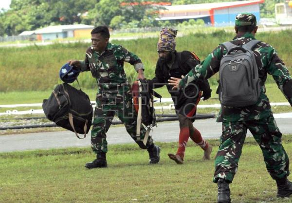 Indonesian military personnel escort a survivor of a shooting through an airport in Timika, Papua, Indonesia, Dec. 06, 2018. EPA-EFE/WAWA KHATULISTIWA