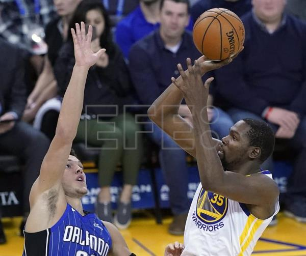 Kevin Durant (d) de los Golden State Warriors en acción ante Aaron Gordon (i) de los Orlando Magic durante un partido de la NBA, entre los Golden State Warriors y los Orlando Magic, en el Oracle Arena de Oakland, California (EE.UU). EFE