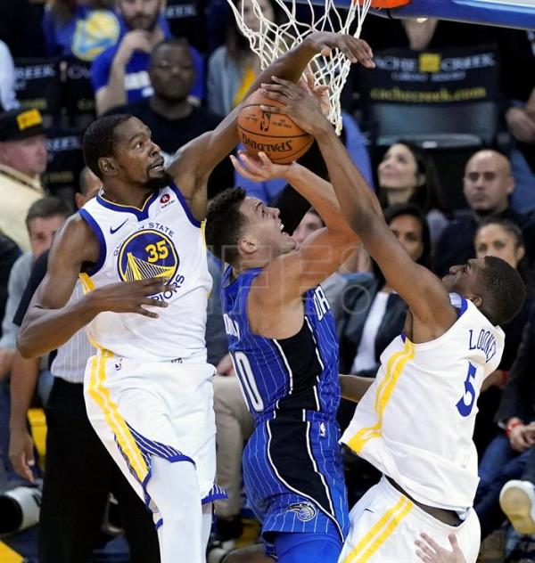 Kevin Durant (i) y Kevon Looney (d) de los Golden State Warriors en acción ante Aaron Gordon (c) de los Orlando Magic durante un partido de la NBA hoy, lunes 13 de noviembre de 2017, entre los Golden State Warriors y los Orlando Magic, en el Oracle Arena de Oakland, California (EE.UU). EFE