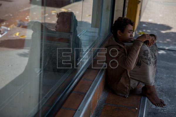A homeless teenager waits outside a bakery in Caracas, Venezuela, Mar. 4, 2018. EPA-EFE/Miguel Gutierrez