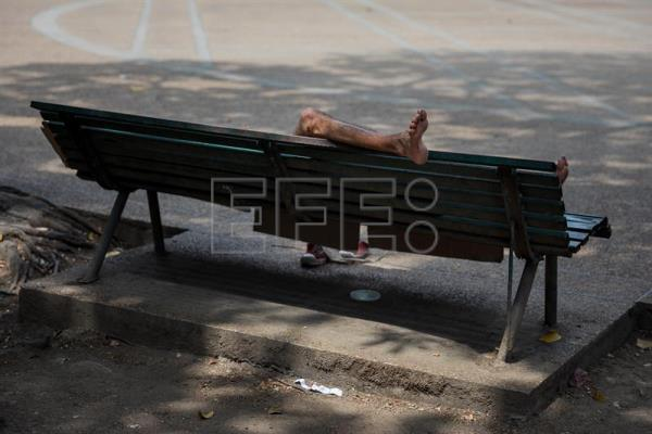 A teenager sleeps on a bench in a square of Caracas, Venezuela, Mar. 4, 2018 EPA-EFE/Miguel Gutierrez