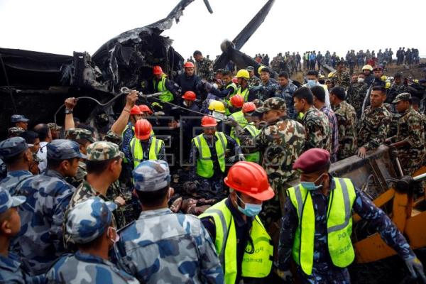 Rescue teams carry a victim from the wreckage of a plane that crashed at the main airport Tribhuvan International Airport in Kathmandu, Nepal, Mar. 12, 2018. EPA-EFE/NARENDRA SHRESTHA