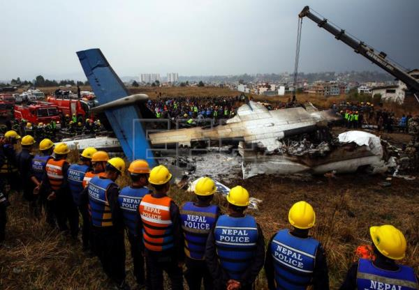 Rescue teams next to a wreckage of a plane that crashed at the main airport Tribhuvan International Airport in Kathmandu, Nepal, Mar. 12, 2018. EPA-EFE/NARENDRA SHRESTHA