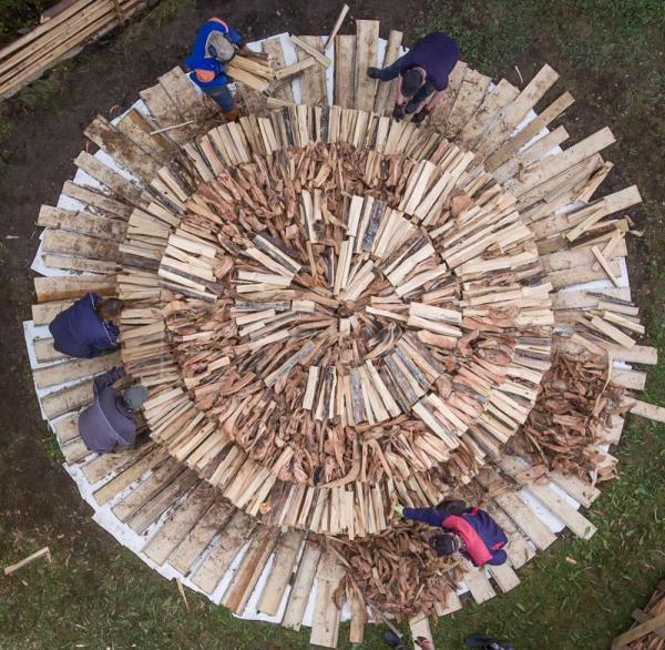 An aerial view of a pine tar pit with villagers and tar heritage enthusiasts stacking chopped 'tervas' wood to pit that is build on the grounds of the Yli-Kirra Outdoor Agricultural Museum in Punkalaidun, Finland, June 27, 2017. EPA/MARKKU OJALA