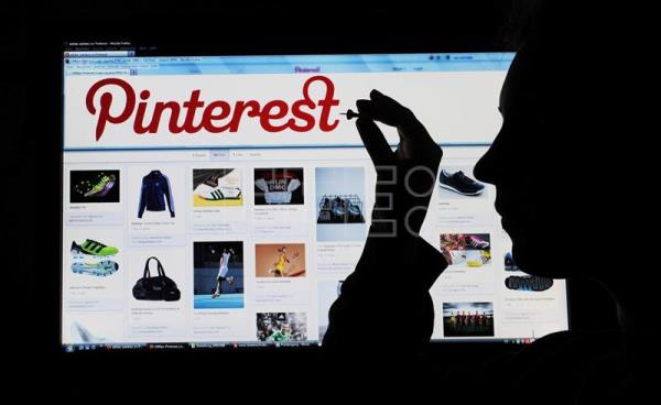 An illustration dated 23 March 2012 shows a woman holding a pin to a computer screen that shows the website of photo-sharing network Pinterest in Hanover, Germany. EPA/JULIAN STRATENSCHULTE