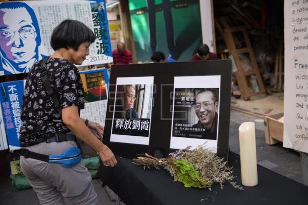 A woman rearranges photos of late Chinese dissident and Nobel Price recipient Liu Xiaobo (R) and his wife Liu Xia (R) in a booth set up by supporters in Hong Kong, China, Jul. 10, 2018. EPA-EFE/FILE/JEROME FAVRE