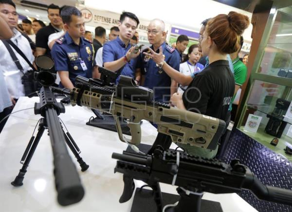 Philippine National Police (PNP) chief Director General Oscar Albayalde (2-R) looks on assault rifles displayed for sale at a gun exhibition in Mandaluyong City, east of Manila, Philippines, Jul. 12, 2018. EPA-EFE/EUGENIO LORETO