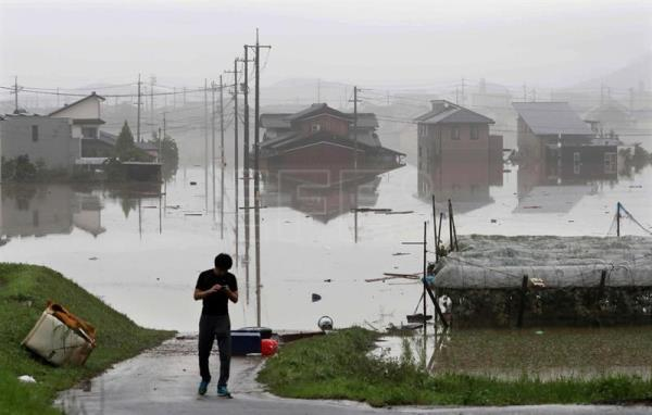 A resident walks past a flooded town in Kurashiki, Okayama Prefecture, western Japan, Jul. 8, 2018. EPA-EFE FILE/JIJI PRESS JAPAN OUT EDITORIAL USE ONLY NO ARCHIVES