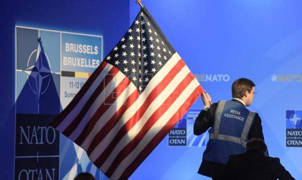 A media assistant brings a US flag into the NATO press briefing room ahead of a news conference of US President Donald J. Trump on the second day of the NATO Summit in Brussels, Belgium, July 12, 2018. NATO member countries' heads of states and governments gather in Brussels on July 11-12, 2018 for a two days meeting. EFE-EPA/CHRISTIAN BRUNA