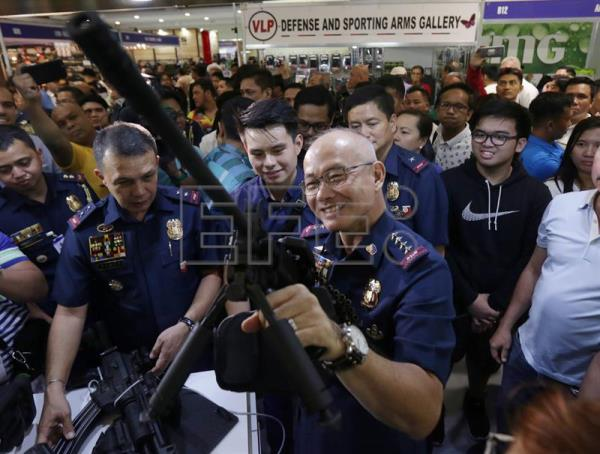 Philippine National Police (PNP) chief Director General Oscar Albayalde holds an assault rifle displayed for sale at a gun exhibition in Mandaluyong City, east of Manila, Philippines, Jul. 12, 2018. EPA-EFE/EUGENIO LORETO