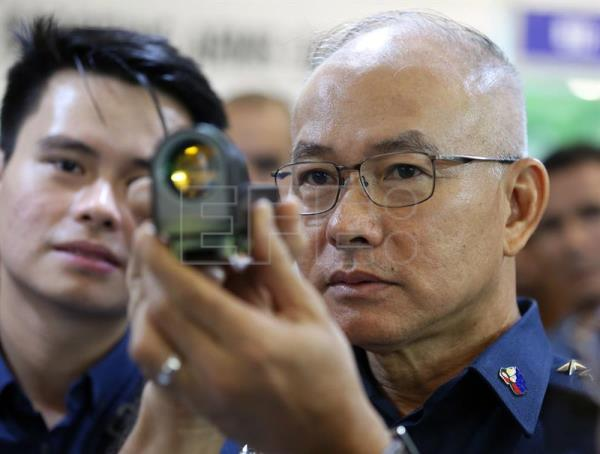 Philippine National Police (PNP) chief Director General Oscar Albayalde (R) holds a sniper rifle scope displayed for sale at a gun exhibition in Mandaluyong City, east of Manila, Philippines, Jul. 12, 2018. EPA-EFE/EUGENIO LORETO