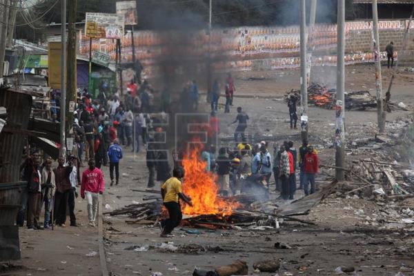 Supporters of the opposition leader Raila Odinga shout slogans after blocking a road by burning tires during a protest in Mathare slum, in Nairobi, Kenya, Aug. 12, 2017. EPA/DANIEL IRUNGU