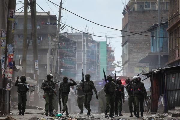 Riot police officers patrol the streets as they open roads blocked by supporters of the opposition leader Raila Odinga during a protest in Mathare slum, in Nairobi, Kenya, Aug. 12, 2017. EPA/DANIEL IRUNGU