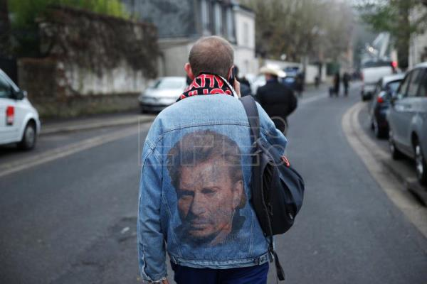 A fan wears a jacket bearing a portrait of the late French singer Johnny Hallyday after his death was announced during the night, in Marnes-la-Coquette, near Paris, France, Dec 6, 2017. EFE-EPA/YOAN VALAT