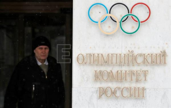 A man walks past the logo of the Russian Olympic Committee at its headquarters in Moscow, Russia, Dec. 6, 2017. EPA-EFE/SERGEI ILNITSKY